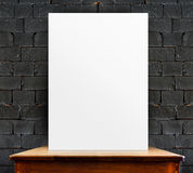 Blank poster on wood table at black brick wall,perspective backg Stock Image