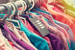 Blank price label on clothes hang on a shelf in a fashion store Royalty Free Stock Image