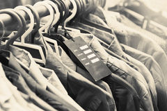 Blank price label on clothes hang on a shelf in a fashion store. Blank price label on clothes hang on a shelf Royalty Free Stock Photography