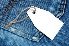 Blank price tag. With copyspace on a jeans texture Royalty Free Stock Images