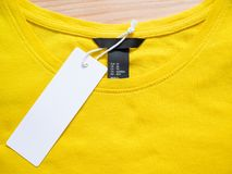 Blank price tag label. On yellow t-shirt stock photo