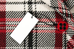 Blank price tag on red checked coat Royalty Free Stock Image