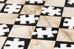 Blank puzzle pieces on chess board Royalty Free Stock Images