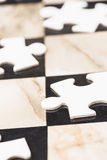 Blank puzzle pieces on chess board Stock Photo