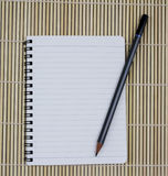Blank realistic spiral notepad notebook with pencil on brown bam Royalty Free Stock Images