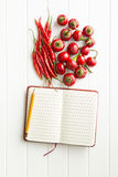 Blank recipe book and hot chili peppers. Top view Royalty Free Stock Image