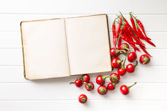 Blank recipe book and hot chili peppers. Stock Images