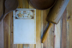 Blank Recipe Card and Wood Kitchen Items. Blank, lined recipe card on wood background with wooden spoon, wood bowl, and wood rolling pin Stock Photo