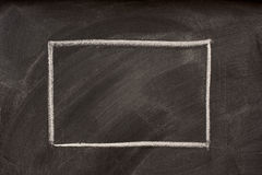 Blank rectangle on a blackboard. Blank rectangle sketched with white chalk on a blackboard with eraser smudges and dust Royalty Free Stock Image