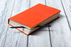 Blank red hardcover book with black pencil on Stock Image