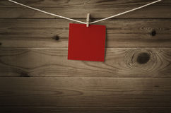 Blank Red Note Paper Pegged to String against Wood Planks. One individual square of festive red note paper, pegged to a string washing line.  Wood plank Royalty Free Stock Photo