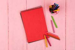 Blank red notepad and crayons on pink wooden table. Blank red note pad and crayons on pink wooden table Stock Images