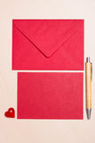 Blank red paper and envelope on table Stock Photos