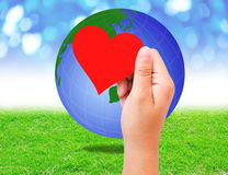 Blank red paper shape in hand and globe on grass background. Stock Photography