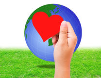 Blank red paper shape in hand and globe on grass background. Royalty Free Stock Photos
