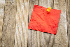 Blank red sticky note on grunge wood. Blank red crumpled sticky note against grunge painted wood - ready for a reminder message Stock Image