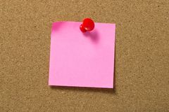 Red note pad attached to corkboard. Blank red sticky note pad pinned to corkboard using a red thumb tack pin Royalty Free Stock Images