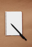 Blank reporters notebook and pencil on a brown pap. Er background Stock Images