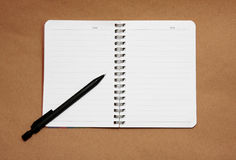 Blank reporters notebook and pencil on a brown pap. Er background Stock Photo