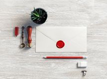 Blank retro envelope. With red wax seal and retro stationery on light wood table background. Mockup for your design. Flat lay stock image