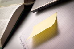 Blank ripped piece of paper with stick note, laptop and book in distance Royalty Free Stock Images