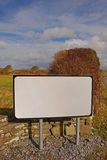 A blank road sign in Ireland Europe. With typical Irish countryside scenery. Originally containing common bilingual road sign in Ireland with English and Irish Royalty Free Stock Image