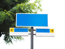 Blank road signboard with black arrow sign over green leaves background. Blank blue and white road signboard with black arrow sign on yellow color over green stock photos