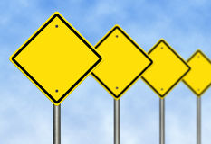 Blank Road Signs. Blank yellow road warning signs over blue sky royalty free stock photos