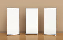 Blank roll-up banners. Against the brown wall Royalty Free Stock Photos