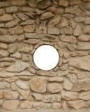 Blank round window on rock wall Stock Photo