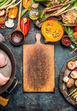 Blank rustic cutting board and Pumpkin with organic vegetables ingredients for tasty cooking on dark kitchen table stock photo