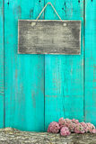 Blank rustic sign hanging on antique teal blue wood fence with log and pink flower border Royalty Free Stock Images