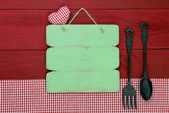 Blank rustic wood menu sign hanging by cast iron spoon and fork and red gingham tablecloth