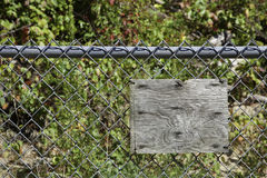 Blank Rustic Wooden Sign on Chain Link Fence. An old blank wooden sign hangs on a gray chain link fence; wooded area and brush behind fence royalty free stock image