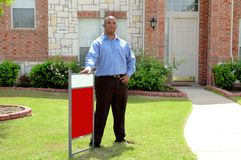 Blank For Sale Sign. Man stands in front yard of this house with sign. He could be buyer, seller, renter or realtor. Sign is blank for your own text Stock Photo