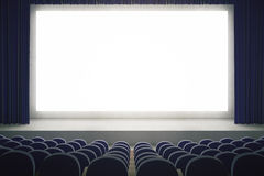 Blank screen in cinema. Movie theater with blank mock up screen. Cinema auditorium with white copy space screen. Rows of seats in cinema theater. Mock up, 3D Royalty Free Stock Image