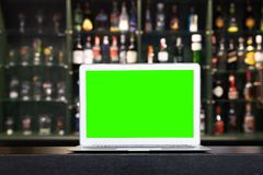 Blank screen of laptop on blur alcohol drink bottle on bar counter in the dark night background. stock images
