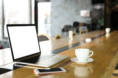Blank screen laptop and cell phone with cup of coffee on wooden table of hipster cafe bar, big windows. Smartphone gadget & notebo royalty free stock photos