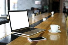 Blank screen laptop and cell phone with cup of coffee on wooden table of hipster cafe bar, big windows. Smartphone gadget & notebo royalty free stock image