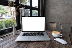 Blank screen laptop computer with latte art coffee. On wooden table, dark background royalty free stock images