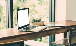 Blank screen laptop computer and tablet on wood stool table near Stock Images