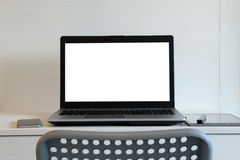 Blank screen laptop computer is on twooden desk Stock Image