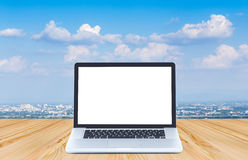 Blank screen laptop computer on wood floor with blue sky backgro. Und Stock Photos
