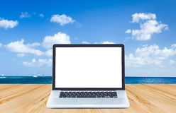 Blank screen laptop computer on wood floor with ocean and blue s. Ky background Stock Images