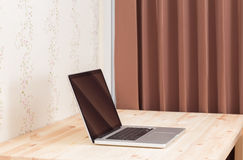 Blank screen laptop computer on wood table Stock Images