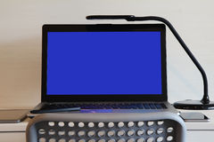Blank screen laptop computer is on wooden desk Royalty Free Stock Images