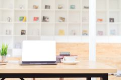 Blank screen laptop mockup on wood table in co-working space and blurred bookshelf background. Blank screen laptop for graphic display montage royalty free stock photos