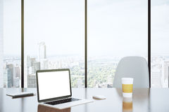 Blank screen of laptop and paper cup on the table with white cha Royalty Free Stock Photography