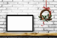 Blank screen laptop on white brick wall with Christmas wreath. Christmas concept, Blank screen laptop on white brick wall with Christmas wreath stock photo