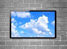 Blank screen LCD tv with blue sky hanging on a wall Royalty Free Stock Photography
